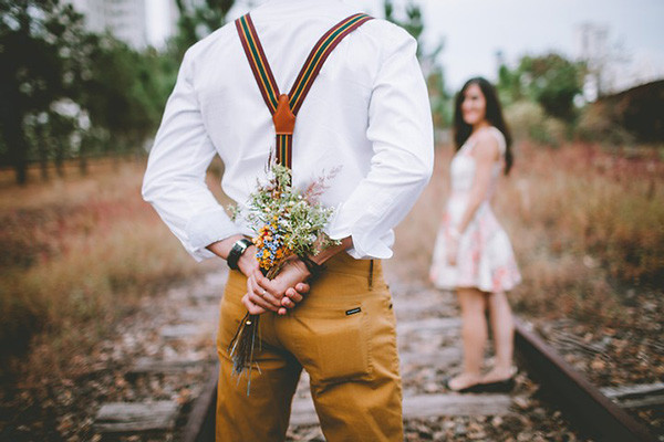 Day date, guy holds a bouquet behind his back