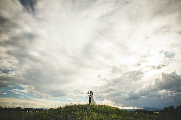 Spring wedding couple under blue sky with clouds