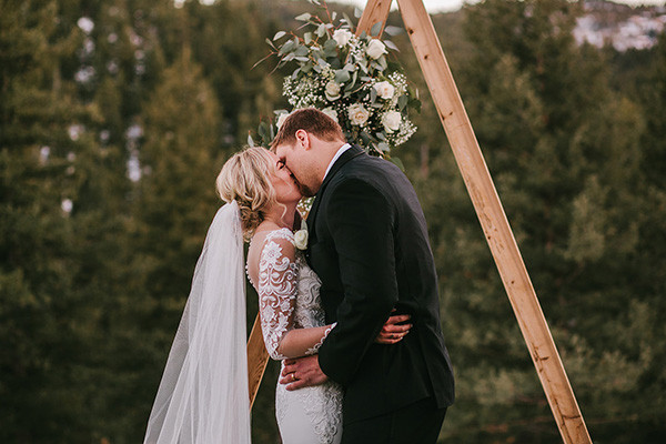 Winter wedding couple kissing in front of arch