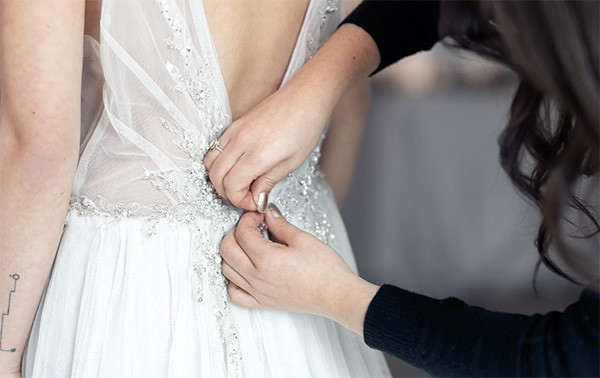 Helping a bride with her wedding gown