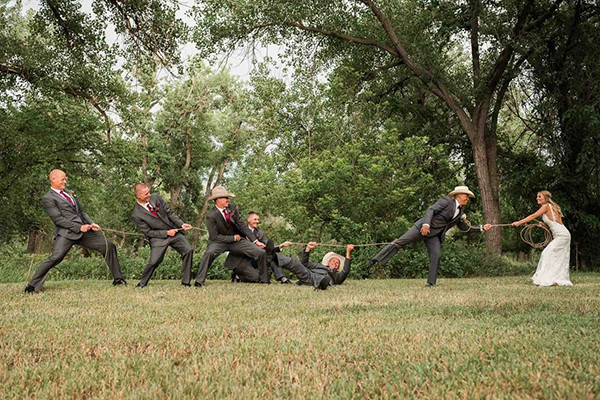 The groomsmen play tug-of-war with the bride!
