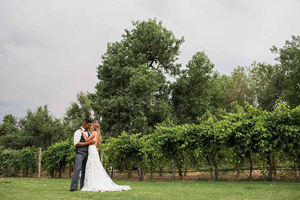 Bride and groom share a private moment by the vineyard